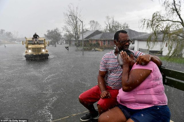 People react as a sudden rain shower soaks them with water while riding out of a flooded neighborhood in a volunteer high water truck assisting people evacuating from homes after neighborhoods flooded in LaPlace, Louisiana