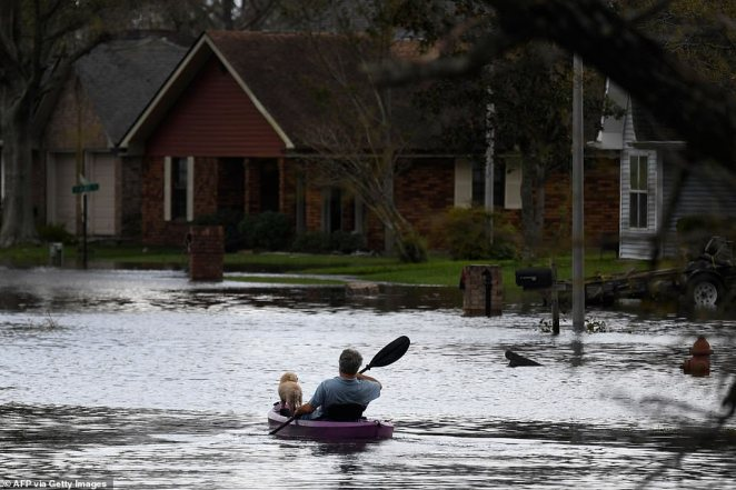 A person kayaks with a dog through flood waters past homes in LaPlace, Louisiana on August 30, 2021 in the aftermath of Hurricane Ida