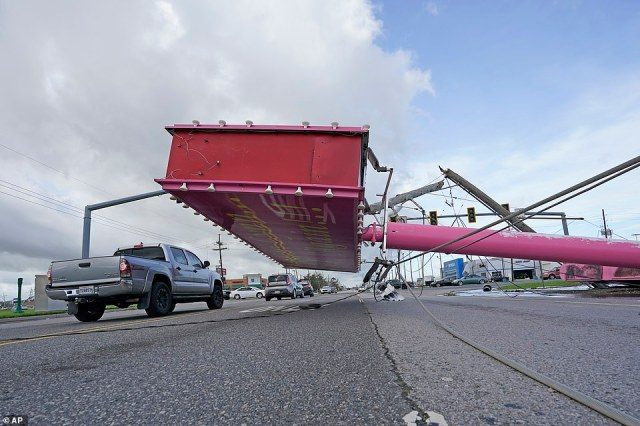 A truck in Houma, Louisiana drives past a metal sign downed by Hurricane Ida's winds on Monday