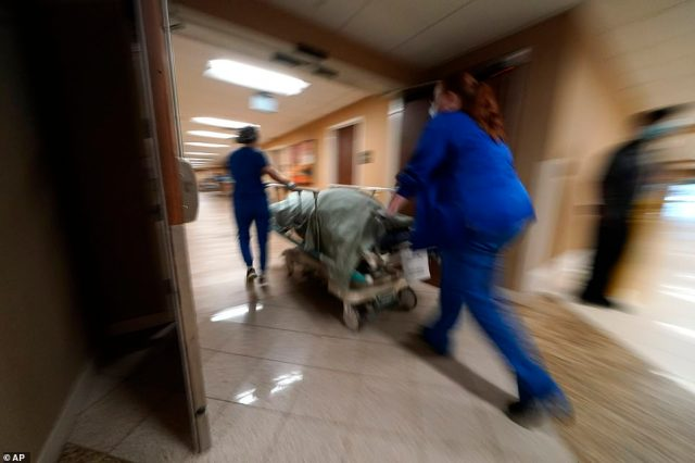 Medical staff in Shreveport, Louisiana are seen moving a COVID victim to a funeral van ahead of Hurricane Ida. There are fears the storm could cause another surge in cases of the virus