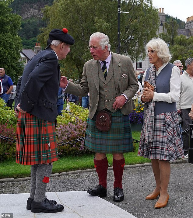 Charles touches the arm of a Scot also clad in full tartan, including a tam o' shanter, a traditional bonnet