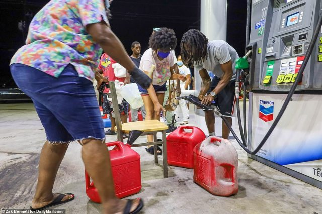 Locals are pictured filling tanks at a Chevron after lining up for hours to get to the pump