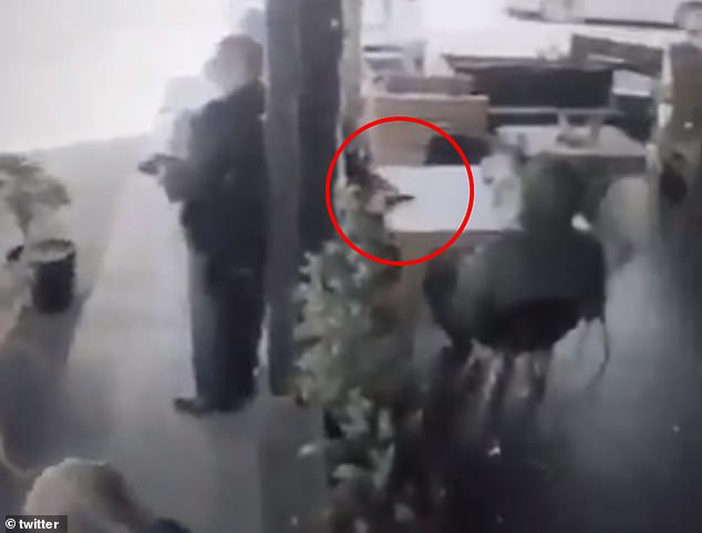 The elderly man disguised as a priest stands next to a pole and places the cellphone on top of a table before his accomplice grabbed it and walked out of the Playa del Carmen restaurant. Both men remain at-large