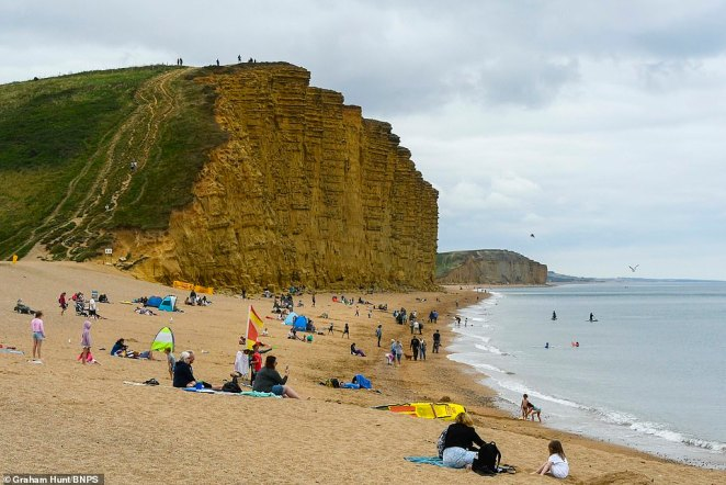 Revellers sit on the beach at West Bay in Dorset as the region is left overcast with grey clouds and forecasters predicts more rain and wind