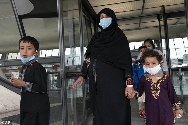 Families evacuated from Kabul, Afghanistan, wait to board a bus after they arrived at Washington Dulles International Airport