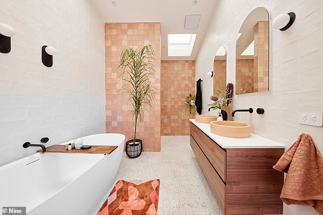 Indulgent: The main bathroom channels 'day spa-type indulgence', according to the listing, with peach-coloured basins, a skylight and underfloor heating