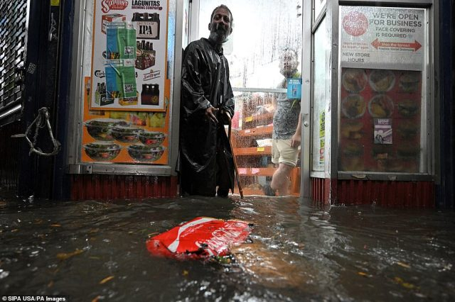 QUEENS, NEW YORK CITY: A homeless man stands in the doorway of a deli during flash flooding caused by storm Ida