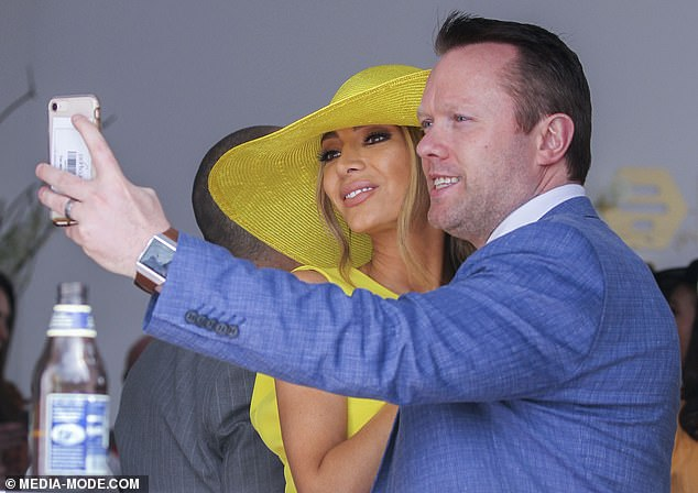 Posing up: At one stage, the mother-of-two and fashion designer posed for happy snaps with a male companion in the exclusive party