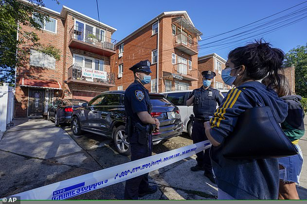 Deborah Torres (right) talks to police as they stand outside her Queens home where her downstairs neighbors drowned in the flood waters caused by Hurricane Ida Thursday, September 2
