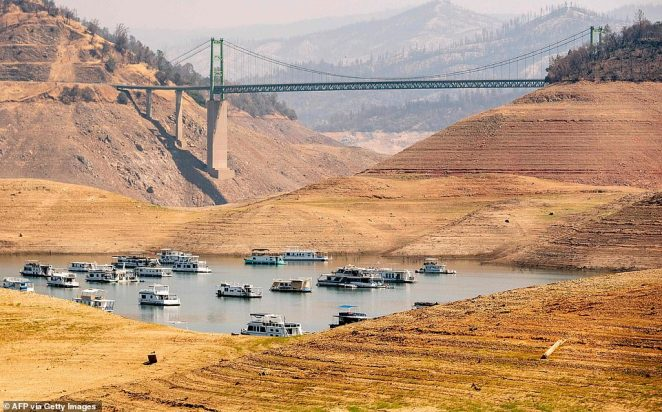 Houseboats sit in a narrow section of water in a depleted Lake Oroville in Oroville, California on September 5, 2021