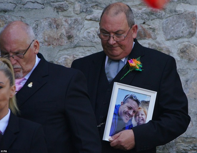 A man carries a photograph of three-year-old Sophie Martyn and her father Lee Martyn from the church in Plymouth today