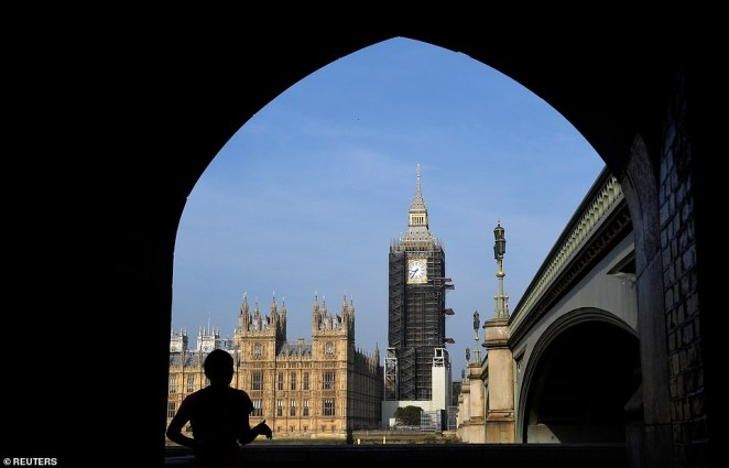 A runner passes through an archway opposite the Elizabeth Tower today as the restoration work continues on the structure
