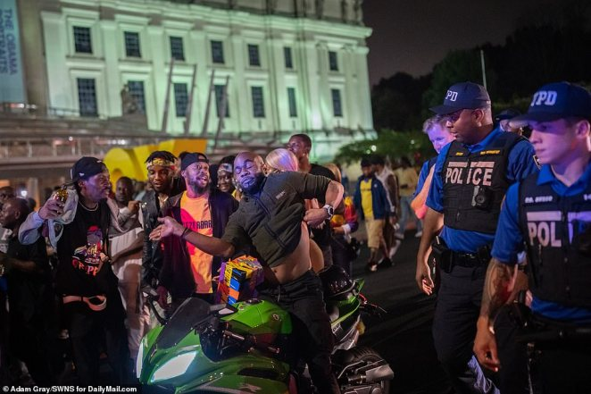 NYPD officers look on as revelers celebrate unofficial J'Ouvert festivities in Brooklyn before dawn on Monday