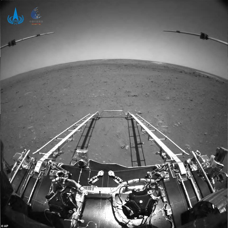 In this black-and-white front shot taken by China's Zhurong Mars rover in May, extension arms and a departure ramp are deployed on the rover's lander on the surface of Mars