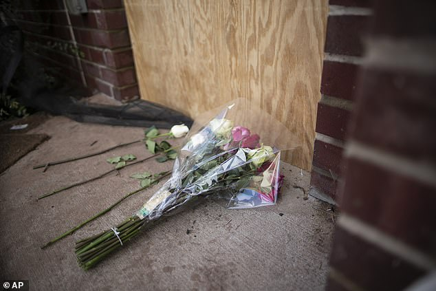 Flowers are seen on a makeshift memorial at the door of one of the four dead victims