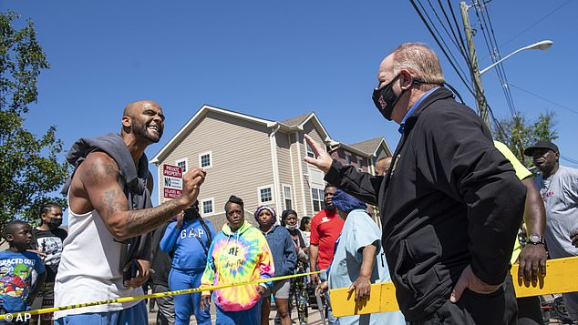 One of the residents is seen arguing with J. Christian Bollwage, right, the mayor of Elizabeth