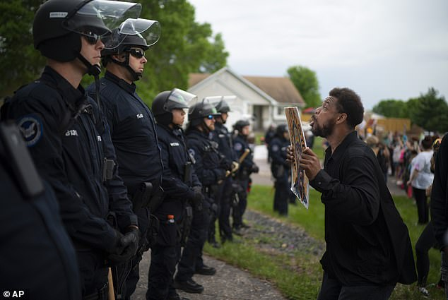 A demonstrator holding a sign jumped up and down in front of a line of police officers outside the Oakdale, Minnesota home of Derek Chauvin on May 27, just two days after he was seen kneeling on George Floyd's neck. The Department of Justice and the city of Minneapolis are now investigating officers' conduct during the protests