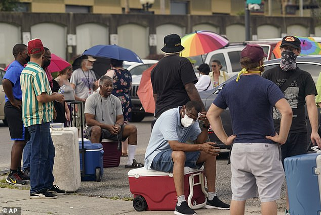 'Things are changing so drastically in terms of the environment,' said President Joe Biden when he visited Hurricane-damaged regions in the state on Friday, linking the storm's severity to climate change. Pictured are New Orleans residents on September 1 seeking out food and relief from the oppressive heat on September 1