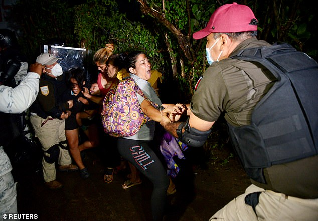 Agents of the National Migration Institute (INM) detain migrants during an operation to dissolve a caravan of migrants and asylum seekers from Central America and the Caribbean