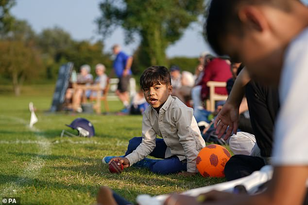 Afghan refugees are settling into life in the UK with a friendly – but fiercely competitive – game of cricket (pictured: Afghan citizen Abdullah watches his father take park in match)