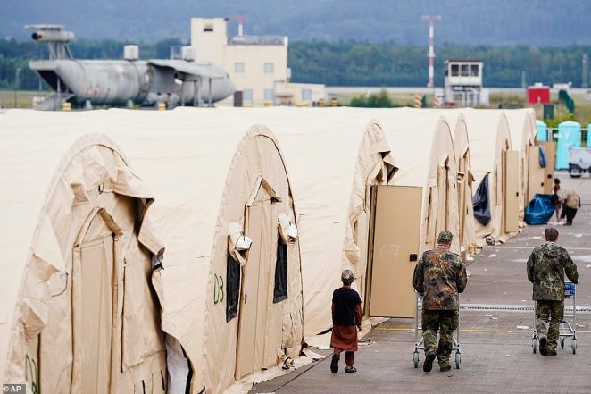 U.S. soldiers walk past a row of tents and a young Afghan evacuee at Ramstein Air Base. Anthony Blinken, the Secretary of State, will visit the base on Wednesday