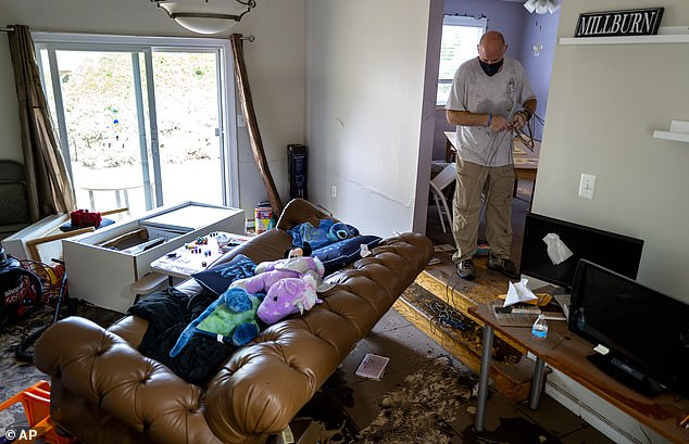 A volunteer works inside the heavily damaged home of the Hossain-Miu family in New Jersey after Hurricane Ida made landfall