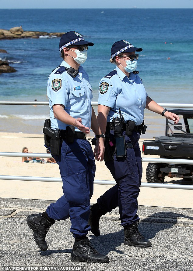 NSW Police officers have until the end of November to receive both Covid-19 vaccine doses. Pictured are two masked officers at Bondi Beach on September 3