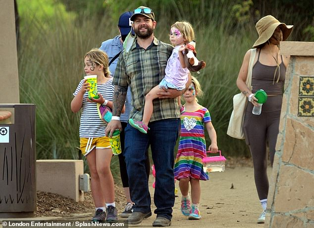 Doting dad: The reality star cut a casual figure in a khaki plaid shirt and navy blue jeans as he carried daughter Minnie, three, in his arms