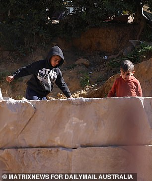Pictured: Climbing over a sandstone wall