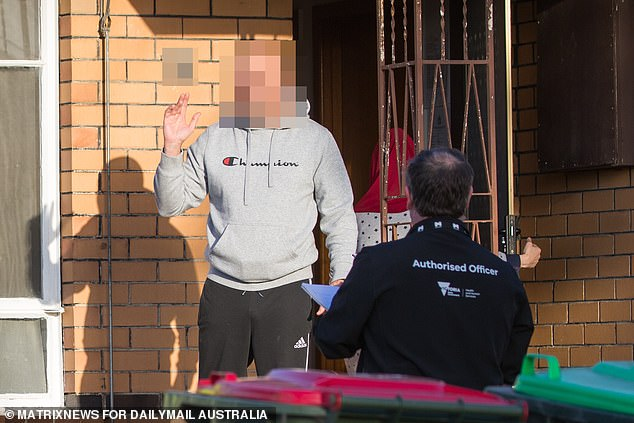 Victorian health officials approach a Covid-infected resident at the door of his Newport property on Monday. The family argued with two officers, complaining that they needed to eat