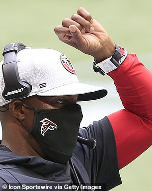 Then-Falcons head coach Raheem Morris raises his wrist with a SafeTag tracking device during a 2020 game