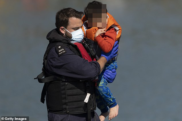 A young migrant boy is carried by a Border Force official after arriving into Dover docks today
