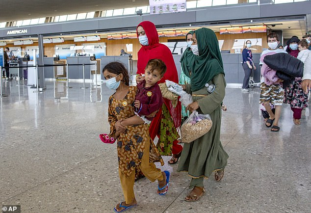 Families evacuated from Kabul walk through Dulles International Airport
