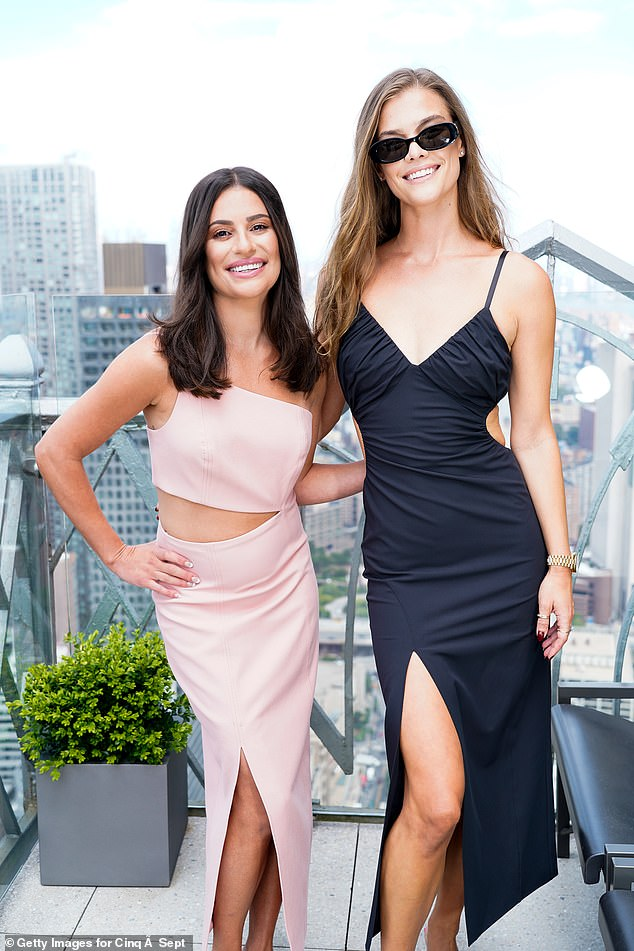 Matching splits:The two young women smiled and embraced each other on a rooftop in front of the New York City skyline