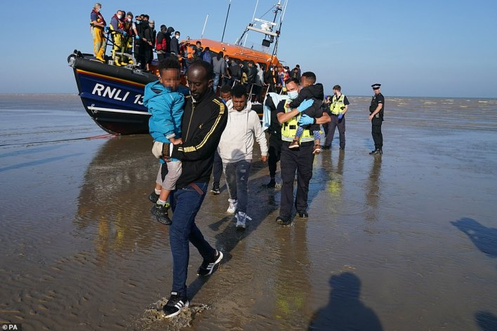 A group of people thought to be migrants are brought ashore from the local lifeboat at Dungeness in Kent, September 7