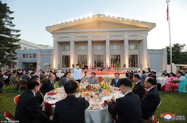 Prior to the parade, a dinner with Kim (centre in grey suit) and others in Pyongyang to celebrate the 73rd anniversary of the country's founding
