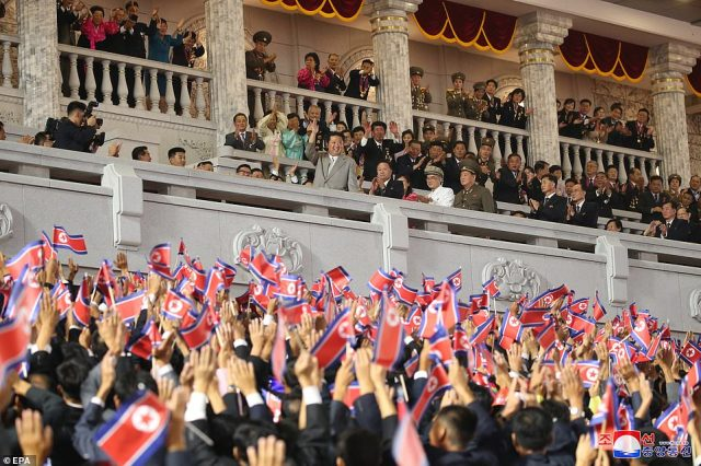 Ecstatic crowds waving the North Korean flag cheer as Kim (centre on balcony) waves during the parade