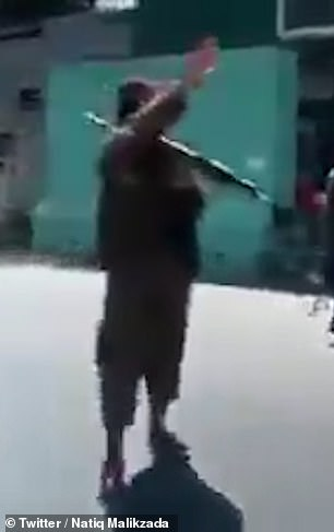 A Taliban member uses a weapon to quell demonstrations