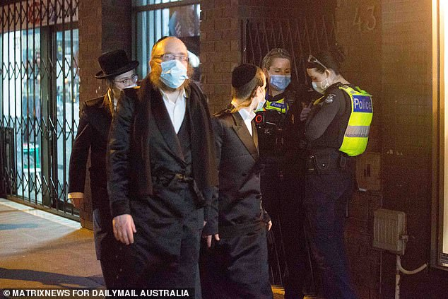 A group of mask-wearing men pass police near one of the gatherings on Tuesday night (pictured)