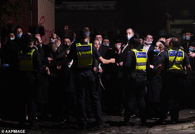 Police speak to worshippers (pictured) at a Jewish New Year's celebration near theAdass Israel Synagogue in Ripponlea, Melbourne, on Tuesday