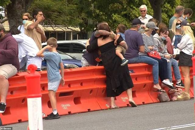 It comes as a border bubble with Queensland restarts for 12 regional NSW areas that are being released from lockdown, allowing students and essential workers with one vaccine dose to enter the Sunshine state from 1am on Monday. Pictured: Families hug across the border on Fathers' Day