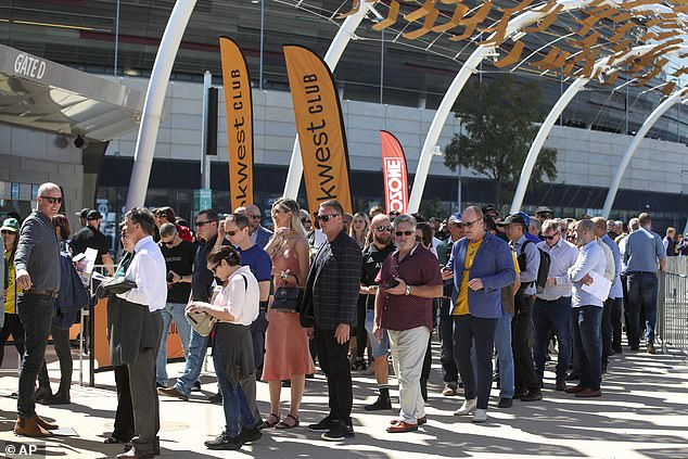 Fans lineup to enter the stadium ahead of the Rugby Championship game between the All Blacks and the Wallabies in Perth, Australia, Sunday, Sept. 5, 2021. While the cities of Sydney and Melbourne in the east have been in strict lockdown, the Western Australia state capital Perth has largely remained open for business behind its closed border