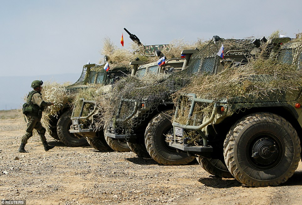 A Russian service member walks towards camouflaged armoured vehicles during huge joint military drills with Belarus