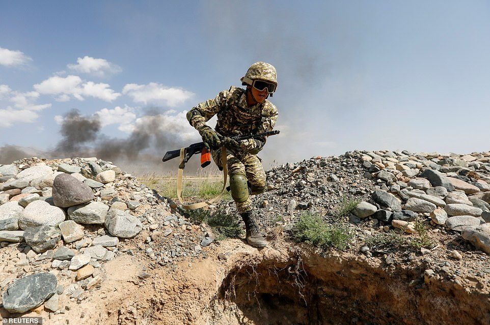 A Kyrgyz soldier takes cover during huge joint military drills with Russia and Belarus, in Putin's latest challenge to the West