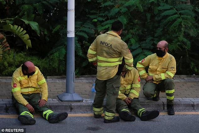 Firefighters take a break after a colleague died while tackling the 'out-of-control' blaze near Costa del Sol resort Estepona