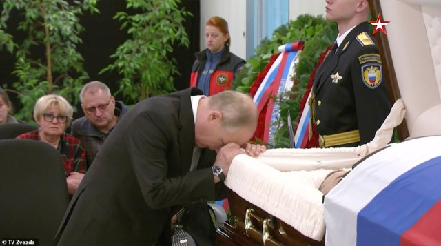 A grief-stricken Vladimir Putin appeared devastated twice resting his head on the open coffin of his emergencies minister Yevgeny Zinichev after died on Tuesday 'trying to save a man'