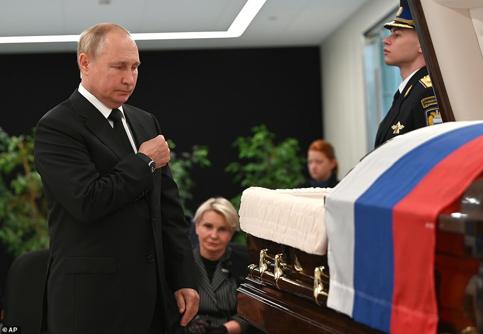 Putin made a cross across his body as he stepped away from the open casket of former emergencies minister Yevgeny Zinichev
