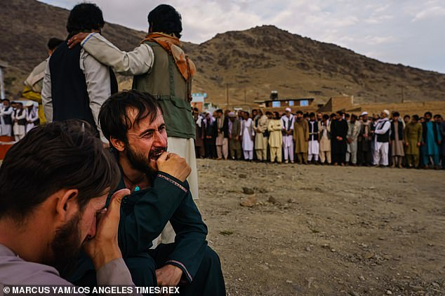 Ramal Ahmadi, second from left, weeps uncontrollably at the mass funeral attended by dozens of friends and family