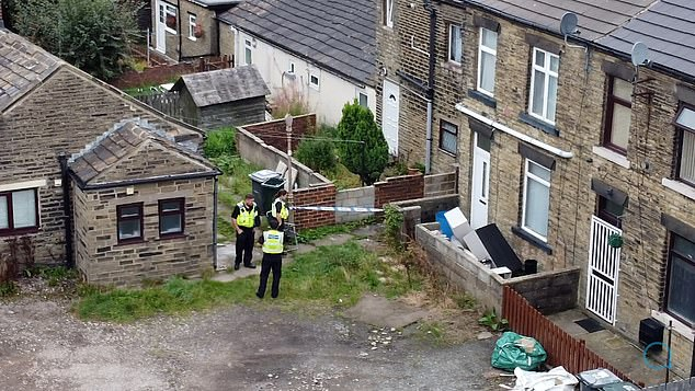 Pictured: An aerial view showing the rear entrance of the alleyway, with three police officers seen standing guard on Saturday