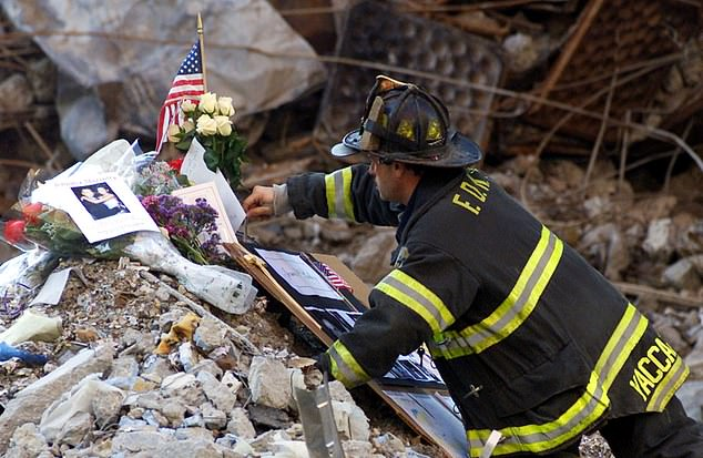 A firefighter leaves mementos for the fallen at the remains of the building in 2001